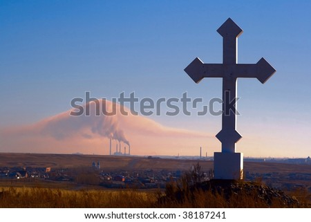 Religion and the industry. A cross and a smoke in the dark blue sky.landscape