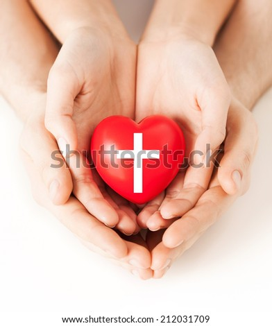religion, christianity and charity concept - family couple hands holding red heart with christian cross symbol - stock photo