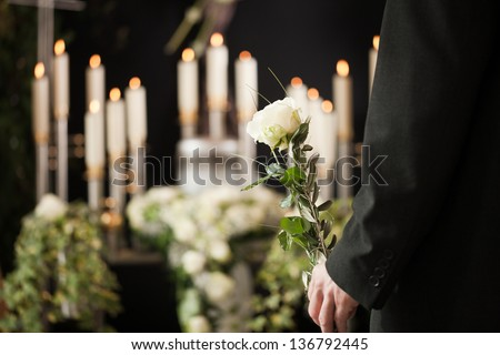 Religion, death and dolor  - man at funeral with white rose mourning the dead - stock photo