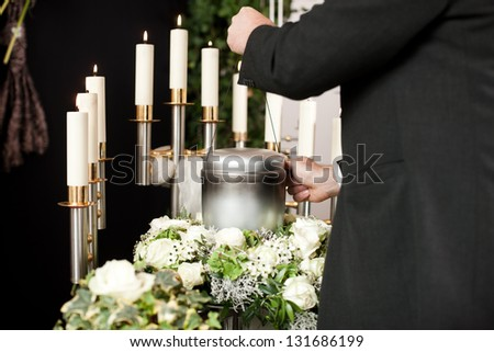Religion, death and dolor  - mortician on funeral with urn - stock photo
