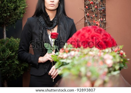 Religion, death and dolor  - woman mourning on funeral with coffin - stock photo