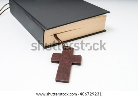 Religion or theology concept. Bible book and crucifix. - stock photo