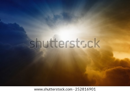 Religious background - bright sunlight from dark red and blue sky, rays of hope - stock photo