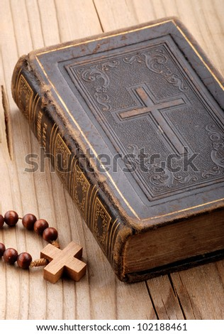 religious book with rosary on the wooden table - stock photo