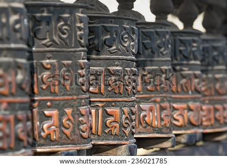 Religious Buddhist prayer wheels (center focus, rest blurred) - stock photo