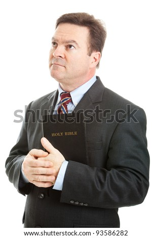 Religious Christian man in a business suit, holding his bible and looking heavenward.  Isolated on white.