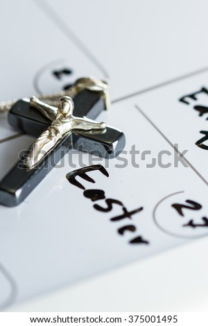 religious cross on a calendar on the date March 27 for a concept for Easter Sunday