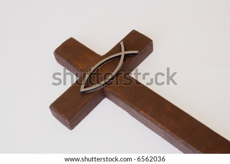 Religious fish sign over wooden cross - stock photo