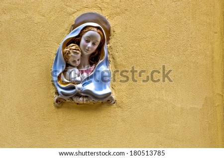 Religious icon of Holy Mary and the child Jesus on stone wall. - stock photo