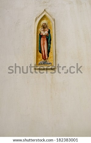 Religious icon of Holy Mary with the baby Jesus on stone wall. - stock photo