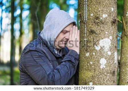 Religious man with a rosary near tree in the park - stock photo