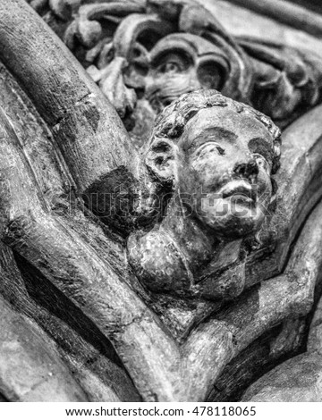 Religious Sculpture on wall two face HDR shallow depth of field black and white vertical photography