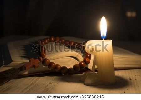 religious theme candle with incense and holy book