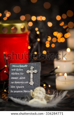 Religious Themed Still Life of Prayer Statue on Altar Illuminated with Lit Candles with Central Copy Space - stock photo