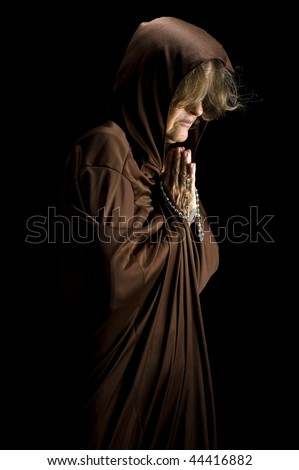 Religious woman praying and holding a rosary - stock photo