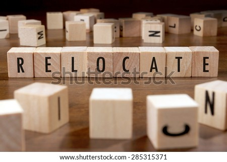 RELOCATE word written on wood block - stock photo