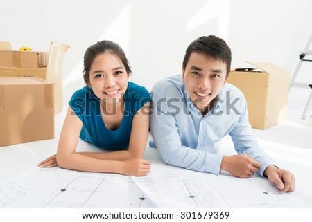 Relocation and renovation: couple lying on the floor with blueprints of the house - stock photo