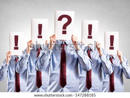 Reluctance businessman holding question mark over his head - stock photo