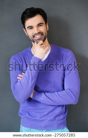 Remaining optimism in any situation. Handsome young man holding hand on chin and smiling at camera while standing against grey background - stock photo