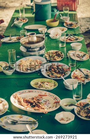 Remaining plates leftover on the table with remaining Thai food in vintage color - stock photo