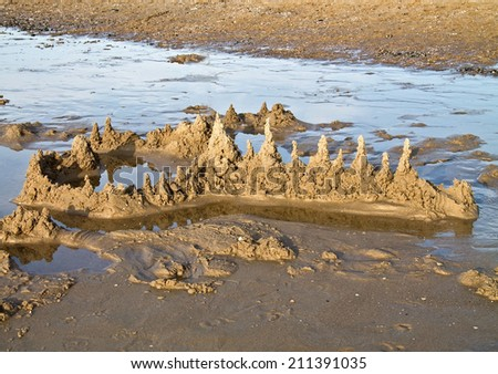 Remains of a washed away sandcastle - stock photo