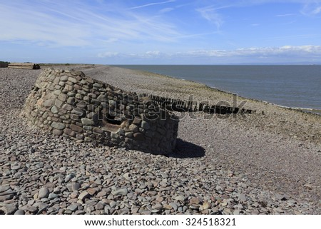 """Remains of a World War II """"Type 24"""" pillbox overlooking Porlock Beach, polygonal in shape with five machine-gun loopholes. It may have been the command post for the area. It has partially collapsed. - stock photo"""