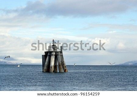 Remains of an old pier pillar in the Kachemak Bay Alaska with seagulls and nice clouds. - stock photo