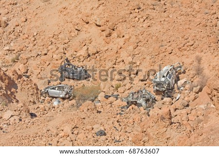 Remains of crashed cars fallen down in mountain abyss. - stock photo