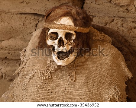 Remains of skull and textiles of ancient Nazca human in tomb at the Cemetery de Chauchilla, Nazca, Peru, South America. - stock photo
