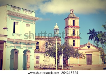Remedios, Cuba - main square palm trees and church. Cross processed color tone - retro style filtered image. - stock photo