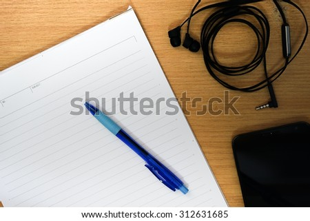 remember notepad List to do with pen ,phone ,earphone on desktop - stock photo