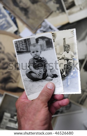 remembering childhood:  man holding photo of himself as a boy - stock photo