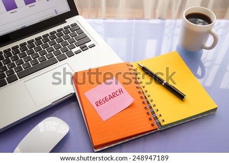 reminder note on paper with text RESEARCH  stick on colorful book with laptop and a cup of coffee on glass table, top view image - stock photo