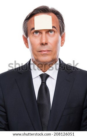 Reminder. Portrait of frustrated mature man in formalwear and adhesive note on his forehead standing against white background  - stock photo