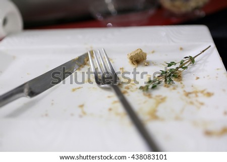 Remnants of food and fork with knife on a plate - stock photo