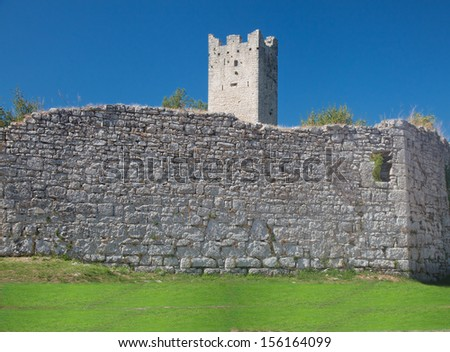 Remnants of medieval city wall and tower abandoned and destroyed in ab. XIII-XV century - stock photo