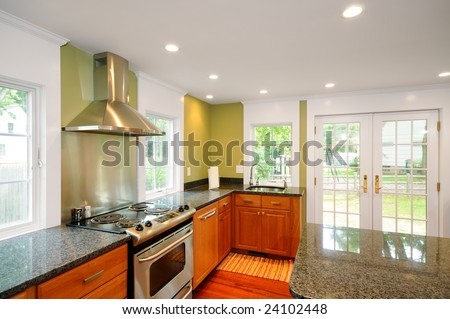 Remodeled kitchen with new granite counter tops, cabinets, doors, windows, exhaust fan and appliances - stock photo