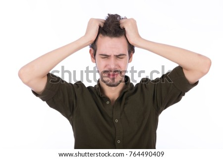 remorseful guy wearing Army green shirt pulling his hair. Isolated on white background.