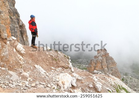 Remote climber standing near a rock wall above clouds, Dolomite Alps, Italy - stock photo