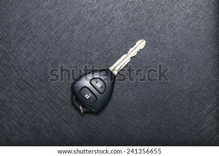 Remote control car key set put on black color leather surface background represent the car security system related equipment. - stock photo