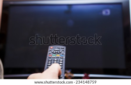 Remote control in a hand is going to change channels - stock photo