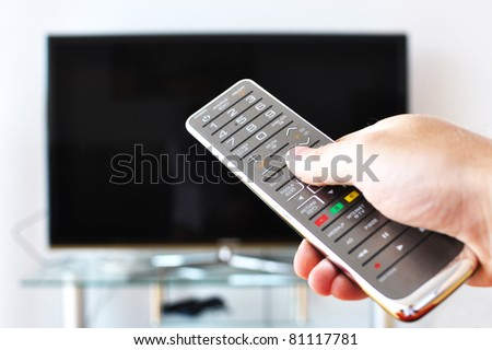 Remote control in the hand against TV screen - stock photo