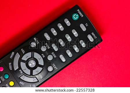 remote control on red background - stock photo