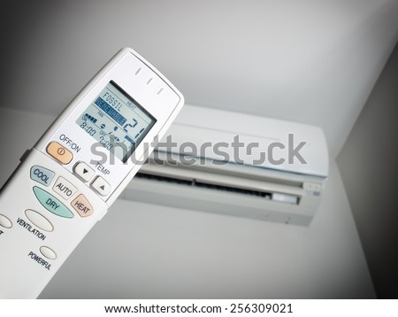 Remote control with two choices of energy source and with an air condition device in the background. - stock photo