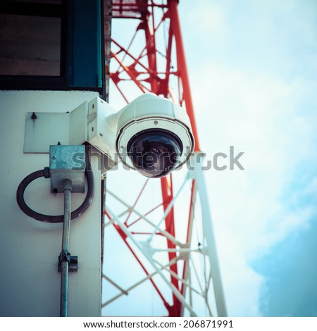 Remote controlled security camera against blue sky, process color - stock photo