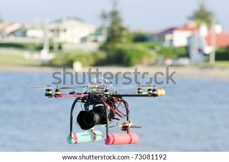 Remote-controlled surveillance helicopter with eight rotors flying over water carrying camera - stock photo