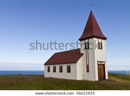 Remote Icelandic Lutheran church on the coast. Typical small simple structure of Icelandic churches - stock photo