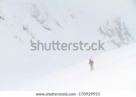 Remote mountaineer, isolated on white snow field