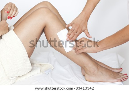 Removing hair from woman's legs - stock photo