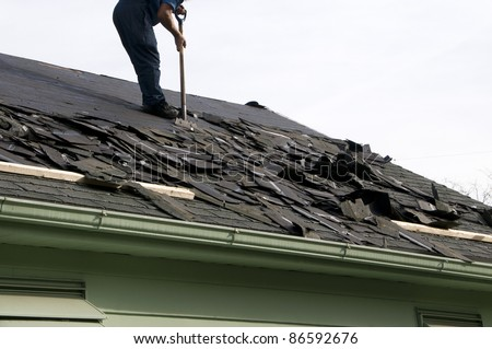 Removing old shingles to prepare a roof for a new installation - stock photo